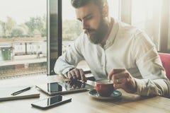 有胡子的商人在办公室坐在桌上,使用片剂计算机 在书桌上是笔记本,智能手机 人工作,学习 免版税库存照片