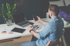 年轻有胡子的商人在办公室坐在桌,饮用的咖啡上和使用智能手机 免版税库存图片