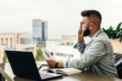 有胡子的商人行家谈话在电话,当坐在书桌在办公室,举行文件,哀伤的看的窗口时 免版税库存图片