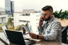 有胡子的商人行家谈话在电话,当坐在书桌在办公室,哀伤的看的文件时 在赢利的秋天 图库摄影