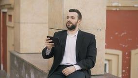 年轻有胡子的商人谈话在开片剂的计算机上录影闲谈业务会议 使用有的app的商人 股票视频