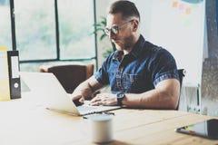 有胡子的图表设计师运作的木桌膝上型计算机现代室内设计顶楼办公室 人工作Coworking演播室 使用 免版税库存照片