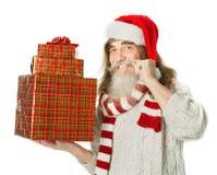 有胡子的圣诞节老人在拿着礼物盒的红色帽子 免版税图库摄影