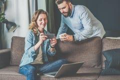 年轻有胡子的在家坐长沙发和在人的手上的男人和妇女看膝上型计算机屏幕 图库摄影