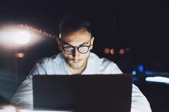 有胡子的在现代顶楼办公室的商人佩带的玻璃工作在晚上 使用当代笔记本发短信的人 库存图片