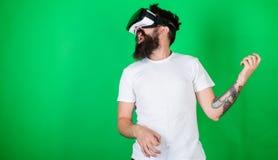 有胡子的在VR玻璃,绿色背景人 热心面孔用途现代技术的行家吉他弹奏者为 免版税库存图片