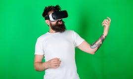 有胡子的在VR玻璃,绿色背景人 热心面孔用途现代技术的行家吉他弹奏者为 库存照片