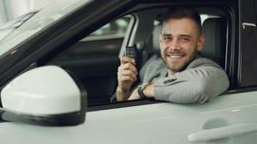 有胡子的坐在美丽的汽车里面的人新的车主特写镜头画象举行关键表链和微笑的看 影视素材