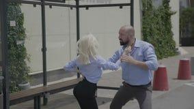 有胡子的坚强的商人和年轻逗人喜爱的妇女街道跳舞拉丁美州的辣调味汁愉快的夫妇在汽车站- 股票录像