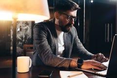 有胡子的学生运作的过程在顶楼办公室在晚上 使用现代膝上型计算机,年轻人开会由与灯的桌坐 免版税图库摄影
