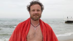 有胡子的年轻人和在海的背景的蓝眼睛有一块毛巾的在他肩膀微笑的调查照相机 4 股票录像