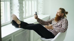 有胡子的年轻在智能手机的行家商人谈的录影闲谈,当坐在与他的腿的offce椅子时 免版税库存图片
