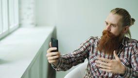 有胡子的年轻在智能手机的行家商人谈的录影闲谈,当坐在offce椅子时 免版税库存照片