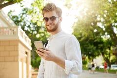 有胡子的年轻正面和微笑的红发在看通过在他的社会网络的太阳镜的人和耳环 免版税库存图片