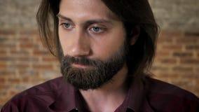 有胡子的年轻深色的人容忍情形,砖背景 股票录像
