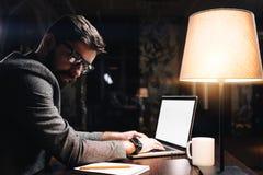 有胡子的年轻键入在当代膝上型计算机的工友佩带的玻璃文本在现代顶楼办公室在晚上 商人由坐 库存图片