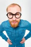 有胡子的恼怒的可笑的年轻人在滑稽的圆的玻璃 图库摄影
