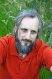 有胡子的愉快的人在绿色背景中坐晴天, potrait 库存照片