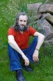 有胡子的愉快的人在绿色背景中坐晴天, potrait 库存图片
