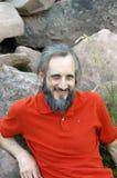 有胡子的愉快的人在绿色背景中坐晴天, potrait 免版税库存图片