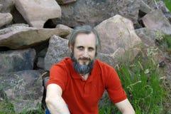 有胡子的愉快的人在绿色背景中坐晴天, potrait 图库摄影