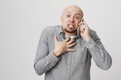有胡子的懊恼和恼怒的秃头欧洲人谈话在电话,当表达憎恶和激怒,握手时 库存图片