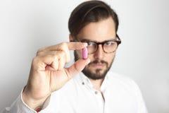 年轻有胡子的拿着桃红色颜色药片的人佩带的白色衬衣玻璃 医学医疗保健人概念照片 成人 免版税图库摄影