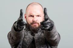 有胡子的指向手指的英俊的人特写镜头  图库摄影