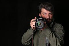 有胡子的摄影师拍照片 关闭 黑色背景 免版税图库摄影