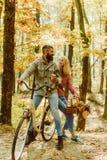 有胡子的放松在秋天森林浪漫夫妇的男人和妇女在日期 日期和爱 在爱乘驾自行车的夫妇 免版税图库摄影