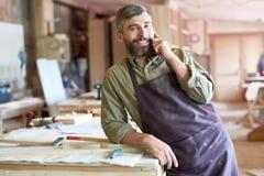 有胡子的木匠讲话由智能手机在现代车间 免版税库存照片