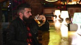 有胡子的残酷在酒吧柜台的人饮用的啤酒 英俊的公在客栈的爱好者观看的体育比赛 股票视频