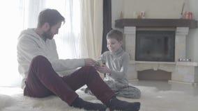 有胡子的爸爸坐与他的小儿子在地毯 父亲同意孩子 男孩计数金钱 父亲儿子 影视素材