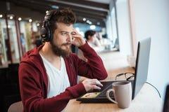 有胡子的男孩使用膝上型计算机和听到音乐 免版税库存照片
