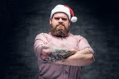 有胡子的男性佩带的圣诞老人` s新年帽子 免版税库存图片