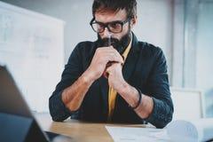有胡子的男性在一个数字式片剂船坞的建筑师佩带的眼睛玻璃工作特写镜头他的书桌的 专业人员 免版税库存图片