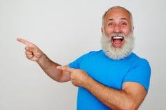 有胡子的男性打手势的幸福和指向与手指对喂 免版税图库摄影