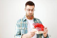 有胡子的男性模型室内射击与在方格的衬衣穿戴的长的厚实的胡子的,打开当前箱子,接受惊奇 库存图片