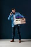 年轻有胡子的男性行家,打扮在牛仔布衬衣,站立户内拿着有花的木箱 免版税图库摄影
