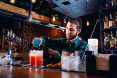 有胡子的男服务员做鸡尾酒在酒吧 图库摄影