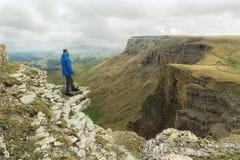 有胡子的站立在岩石边缘和调查在一个史诗高原的距离的行家旅游人 的treadled 库存图片
