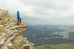 有胡子的站立在岩石边缘和调查在一个史诗高原的距离的行家旅游人 的treadled 免版税库存图片
