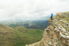 有胡子的站立在岩石边缘和调查在一个史诗高原的距离的行家旅游人 的treadled 免版税库存照片