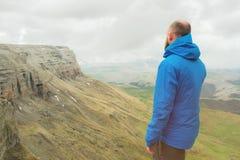 有胡子的站立在岩石边缘和调查在一个史诗高原的距离的行家旅游人 的treadled 库存照片