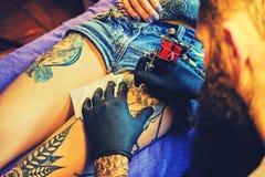 有胡子的纹身花刺男性艺术家在一条女性腿做纹身花刺 免版税图库摄影