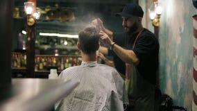 有胡子的美发师喷洒的水和梳他的男性客户的湿头发在一间减速火箭的时髦的理发店 男性发型 股票录像