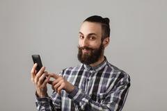 有胡子的英俊的人由在蓝色被摆正的衬衣的电话聊天 库存照片