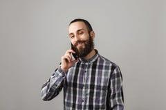 有胡子的英俊的人由在蓝色被摆正的衬衣o的电话谈话 免版税库存图片