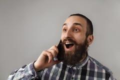 有胡子的英俊的人由在蓝色被摆正的衬衣o的电话谈话 免版税图库摄影