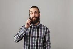 有胡子的英俊的人由在蓝色被摆正的衬衣o的电话谈话 库存照片